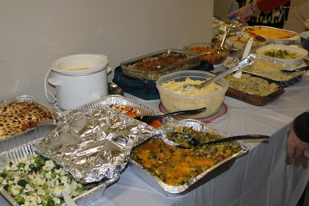 "Classic potluck spread consisting of casseroles in aluminum. Casseroles in corningware. Casseroles in pyrex. (duplicate candied sweet potato casserole... so embarrassing). Note the mashed potatoes with the lid underneath the bowl AS IF there will be any left over to pack up and take home. Everyone hates whoever brought the broccoli and cauliflower ""salad"" and the crock pot is a sign of professionalism... this ain't their first potluck."
