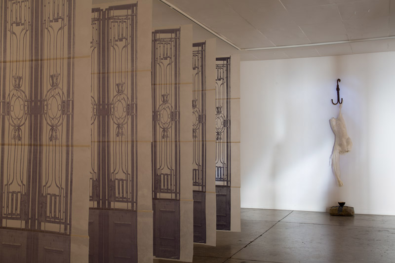 The Seven gates at the Entrance to the Underworld ( foreground) , Inanna Hanging on the Hook  (background), 2014, gates screen printed on Japanese paper, 2,300x98cm, encaustic treated moulded silk paper and tarlatan body of Inanna, metal hook, sandstone with beaten lead.