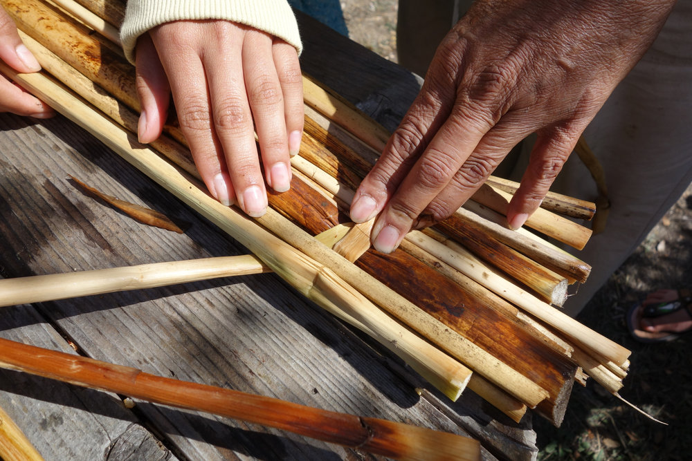 Hands of master basket weaver Kathy Wallace (Yurok/Karuk/Hoopa/Mohawk) and youth making Tule mats