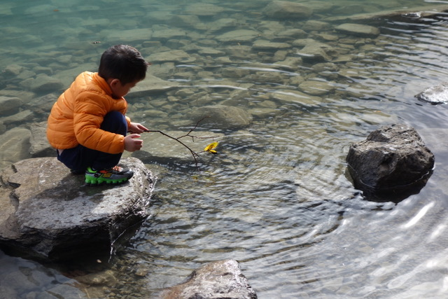 Young Native boy playing at Isabella Lake, Banff National Park, Alberta, Canada