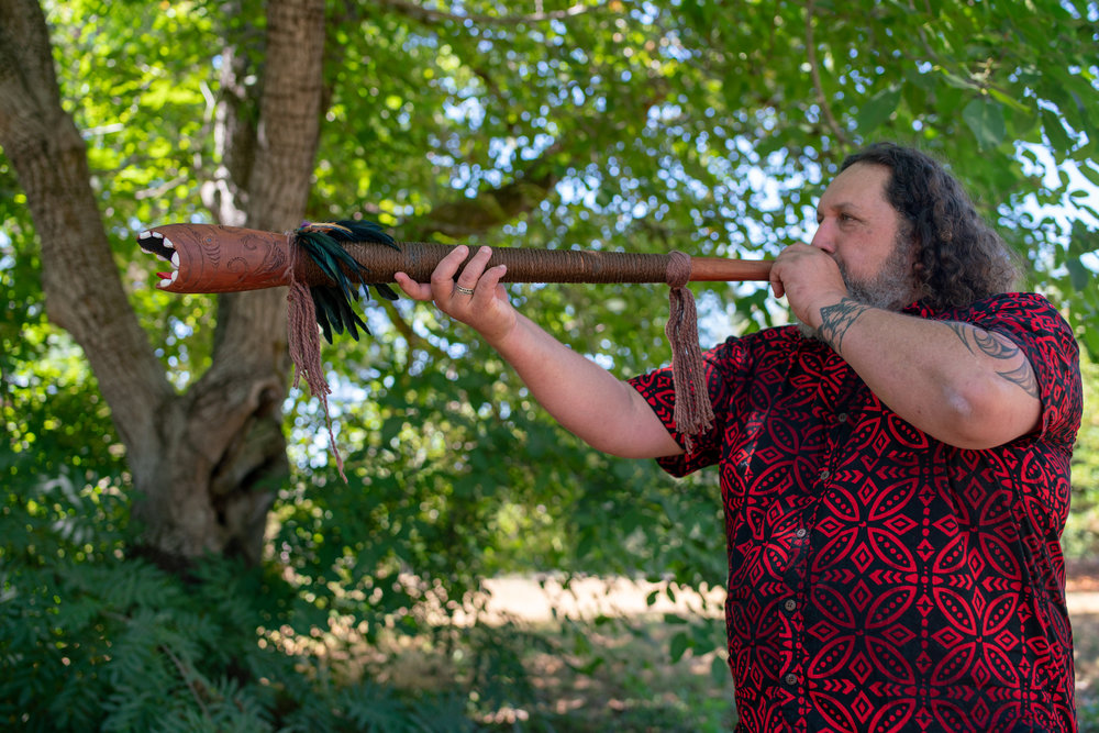 Maori master carver Wikuki Kingi gives the breath of life to his creation, a traditional horn, on land in Sonoma County being blessed as a potential site for an indigenous biocultural oasis.