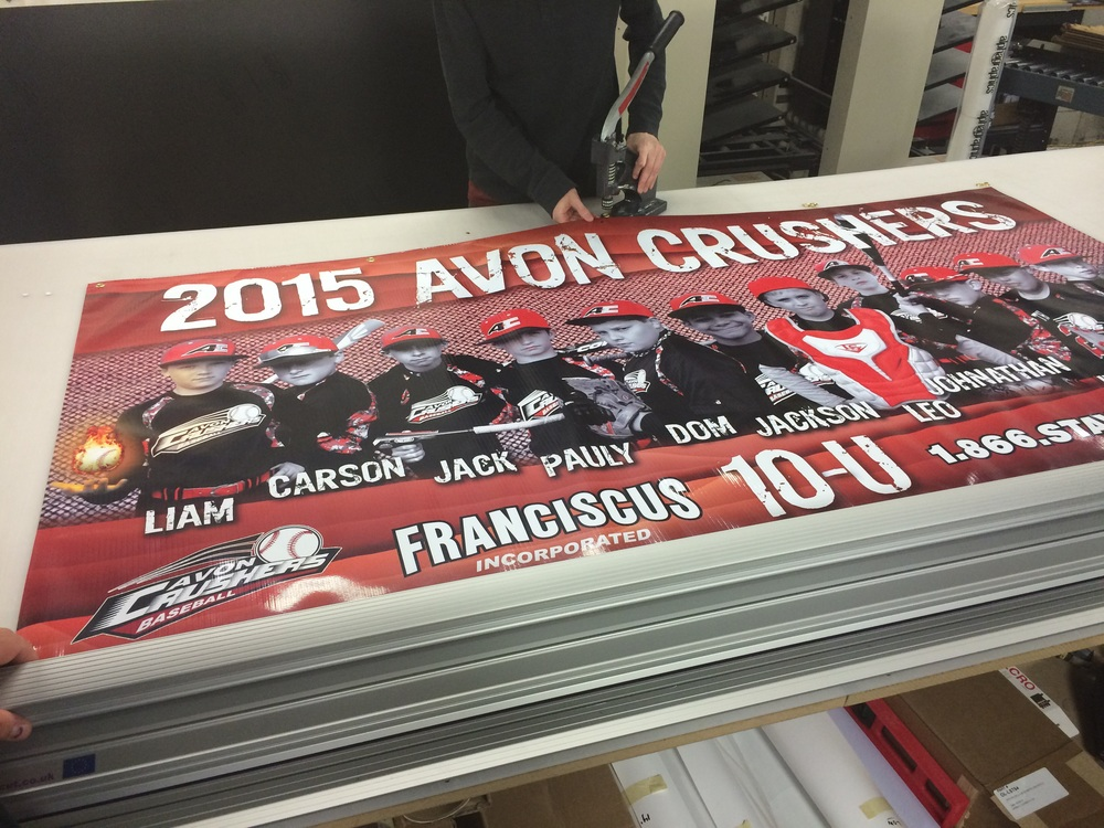 Matt's grommeting the banner ready to be hung on display.