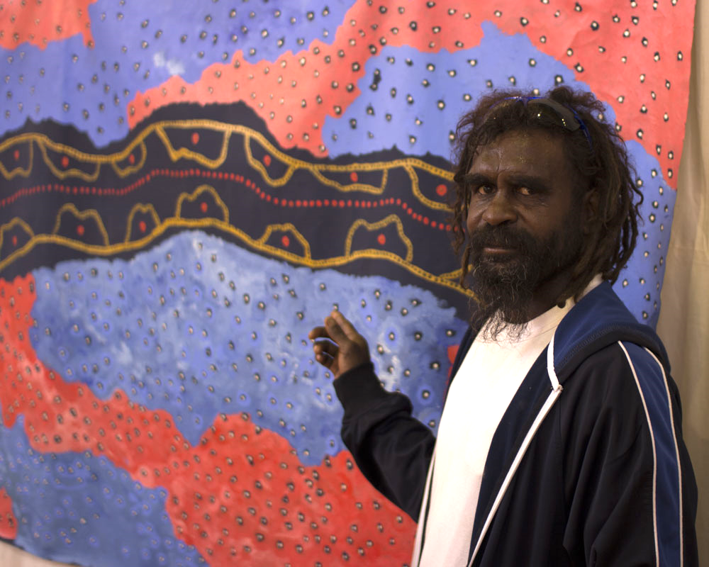 "ARTIST Troy Chapman with his artwork ""Malcolm Dam"". Mr Chapman won the Overall, and Aboriginal Artwork prizes"