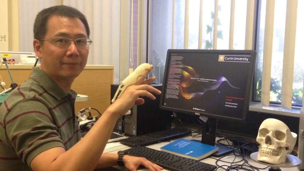 Dr Lei Cui with a prototype of the 3D printed finger orthosis. Dr Cui's team was awarded a $15,000 prize