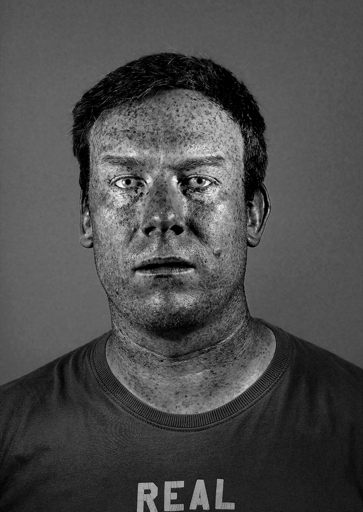 I read an article about a photographer, whose name now escapes me, who shot portraits of black, white & coloured people in South Africa in UV light.  The effect pretty much negates the original skin tone and shows up skin blemishes and images.  This is my version, albeit photoshopped to get the same effect and not shot under UV.