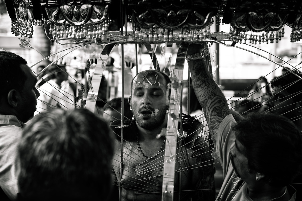 Though still attached to his vel-kavadi, this man has had the mouth-skewers removed. Despite friends & helpers all desperately asking questions and hurrying to remove the spears still piercing his skin he seemed absolutely oblivious to everyone. Sweat & blood ran down his entire body.