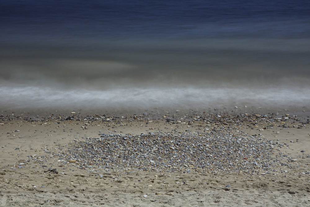 A long exposure photo of the ocean shot at f8 on a bright, sunny day using a 10-stop ND filter. The mist-like appearance of the sea is offset by the sharp, crisp detail in the pebbles.