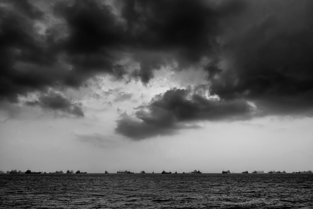 "I used exposure compensation to really bring out the sky and silhouette these ships in the Singapore Straits before converting using my custom ""apocalyptic monochrome"" preset in Silver Efex Pro 2"