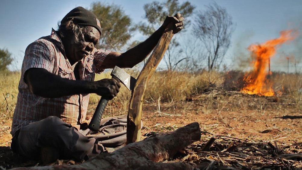 """25 June, 2012 - Wirrimanu   Wirrimanu Elder Bonnie crafting a """"Number 7"""" boomerang at Men's Camp"""