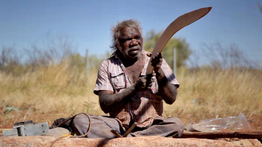"""26 June, 2012 - Wirrimanu   Wirrimanu Elder Bonnie crafting a """"Number 7"""" boomerang at Men's Camp"""