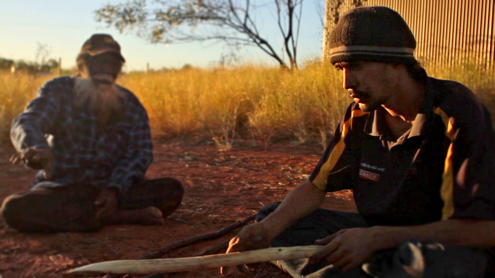 25 May, 2012 - Wirrimanu   Brandy Tjungurrayi instructs his nephew Azman in fashioning a spear at Men's Camp. This is the last known photograph of Brandy as he passed away two days later.