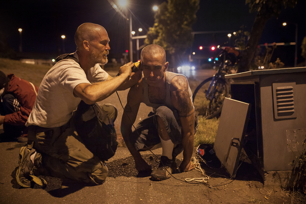 """1 September, 2013 - """"Nickelsville"""", Seattle   Eviction day. Moved on from Nickelsville, residents gather on Highland Park Hwy adjacent to their former home. Two men lift electricity from a park sprinkler system for a haircut."""