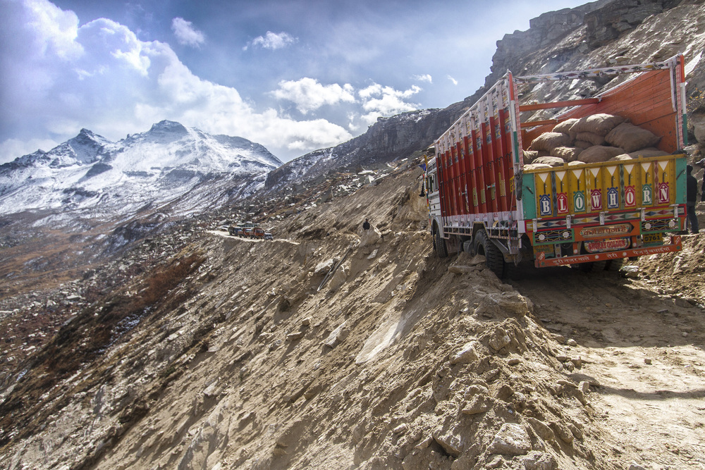 13 October, 2012 - Ascent to Rohtang Pass   Landslides in Spiti Valley occur almost daily resulting in long stoppages and travelers often having to collaborate loading and unloading weighed down trucks, reinforcing roads with gathered stones or towing vehicles back from the precipice.