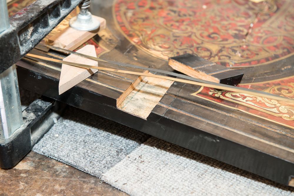 Messing- und Holzteile werden mit Fischleim neu gefestigt.