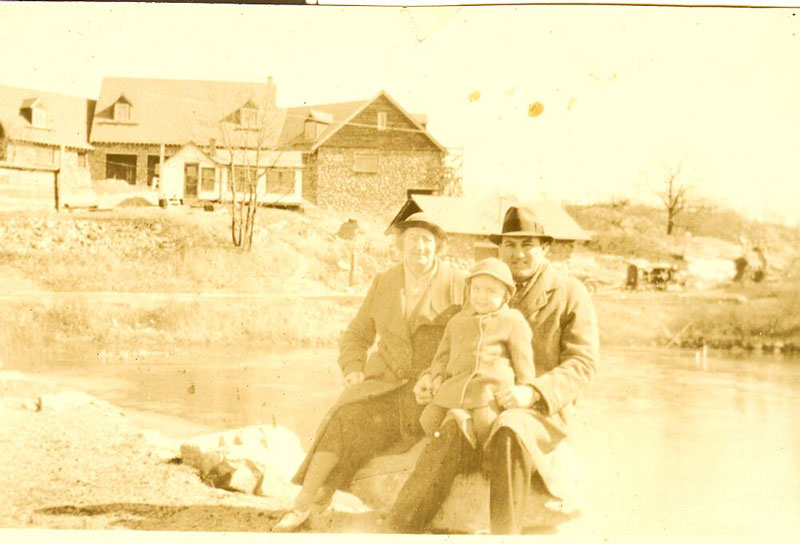 Clubhouse being Built late 1930's. Seated on a rock at First Pond is Golf Pro Roland Hancock, his wife and child.