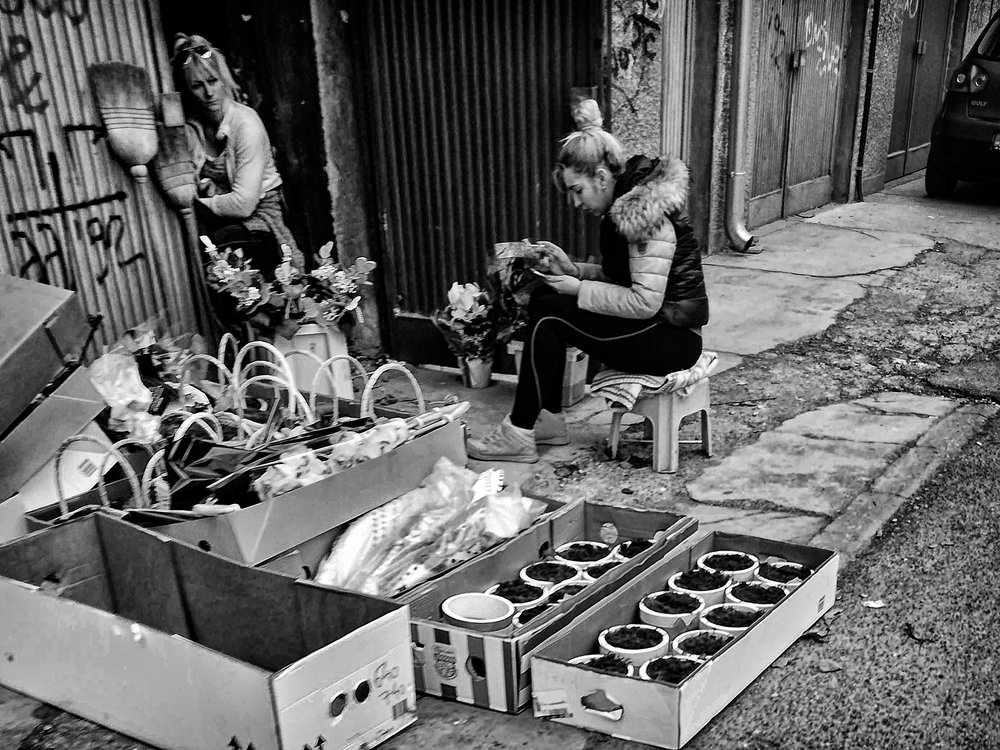 Two women in front of the garage, preparing flowers for selling on a Woman's day.
