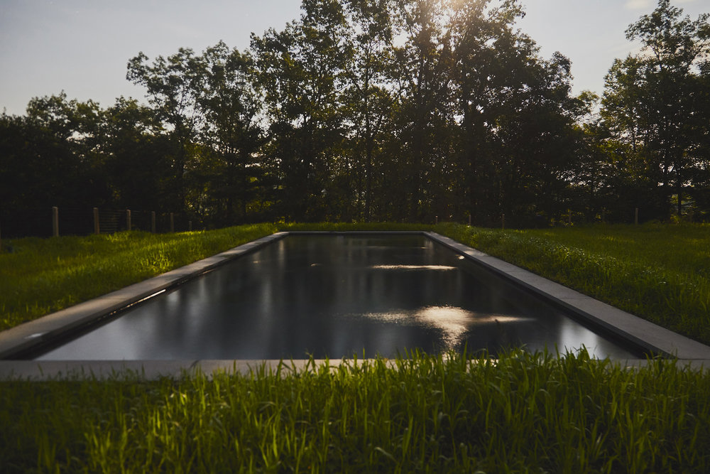 A heated inground swimming pool sits in a courtyard-like field between the main house and carriagehouse