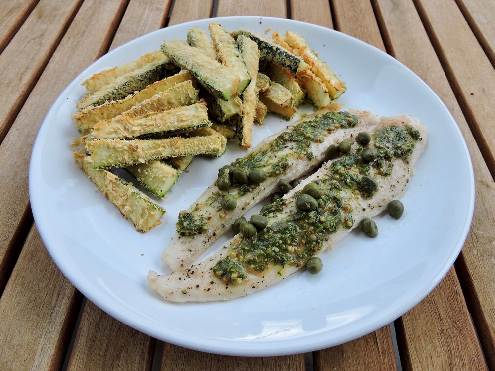 Baked white fish with capers, dill sauce, and zucchini fries.