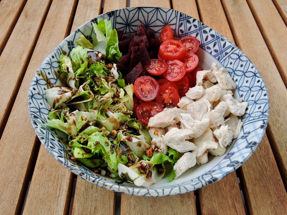 Salad with greens, chicken breast, beets, and tomatoes.