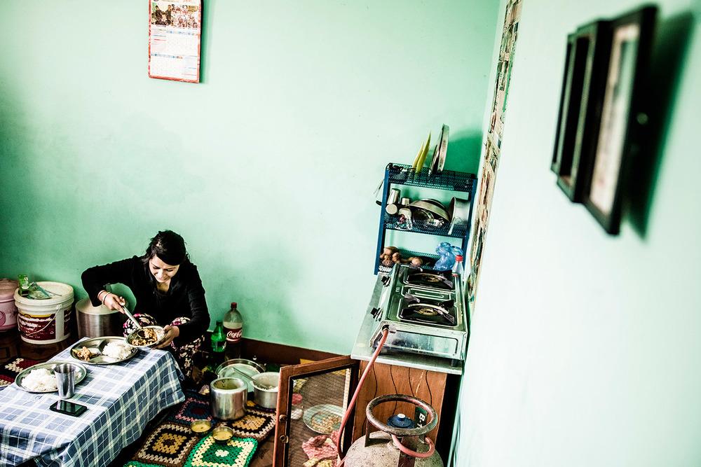 Sanita valmistaa lounasta keittiössään.