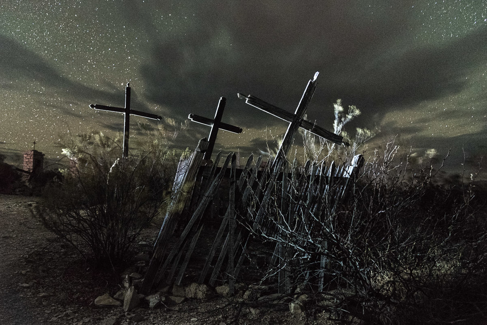 Tres Cruces, Terlingua, 2016.  ISO 6400, 30 seconds, f/4.5. Nikon D750, Nikon 24-120mm f/4 lens at 24mm, Coast HP7 flashlight (back-lighting) and Coast HP3 flashlight (fence lighting). New moon.