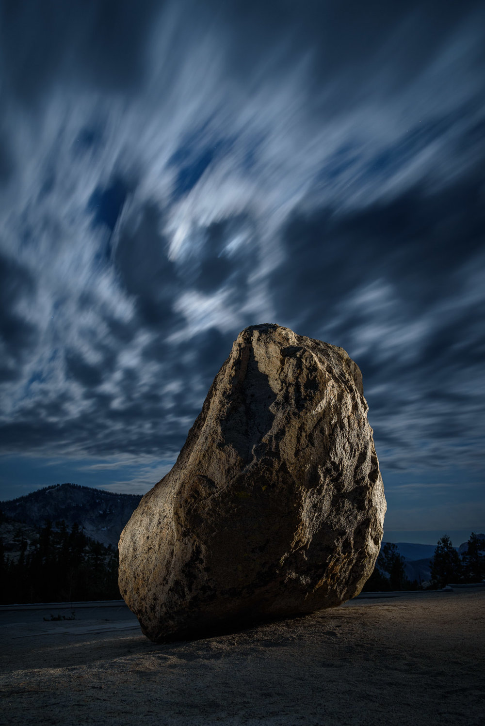 Steve's Rock, Olmsted Point, Yosemite National Park. 30 seconds, f/5.6, ISO 800. Clouds back-lit with moonlight high in the Sierra with light from a  Coast HP5R  filtered with two gels, a  1/2 CTO  and a  1/8 minus green .