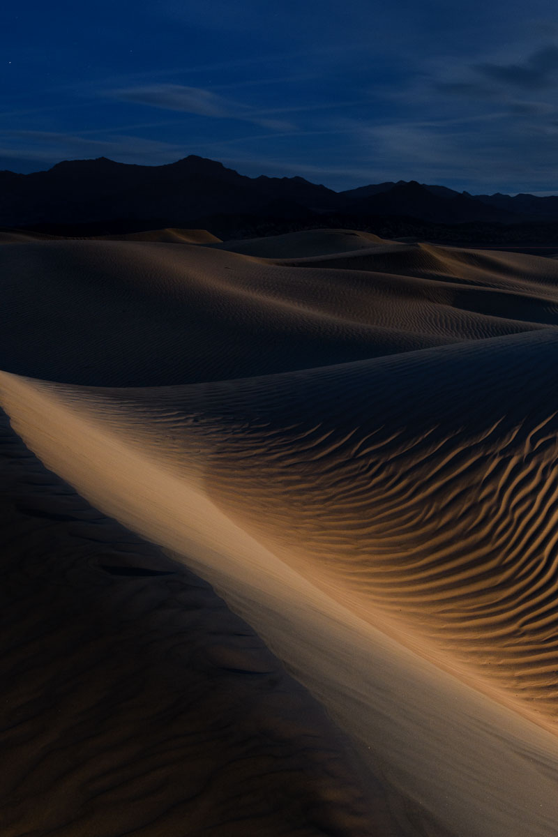 Mesquite Flat Sand Dunes, Death Valley National Park. The moon is low in the sky and the ambient exposure is intentionally underexposed for effect. For the middle-ground dunes, warmth, exposure and contrast were boosted using a  local adjustment brush  in Lightroom. An example of the malleability of files from this camera. Nikon D850,  Nikon 24-120mm f/4  lens at 34mm, and  Luxli Constructor LED light  at 3200 K on the lowest setting, placed at the toe of the foreground dune. 30 seconds, f/10, ISO 800.
