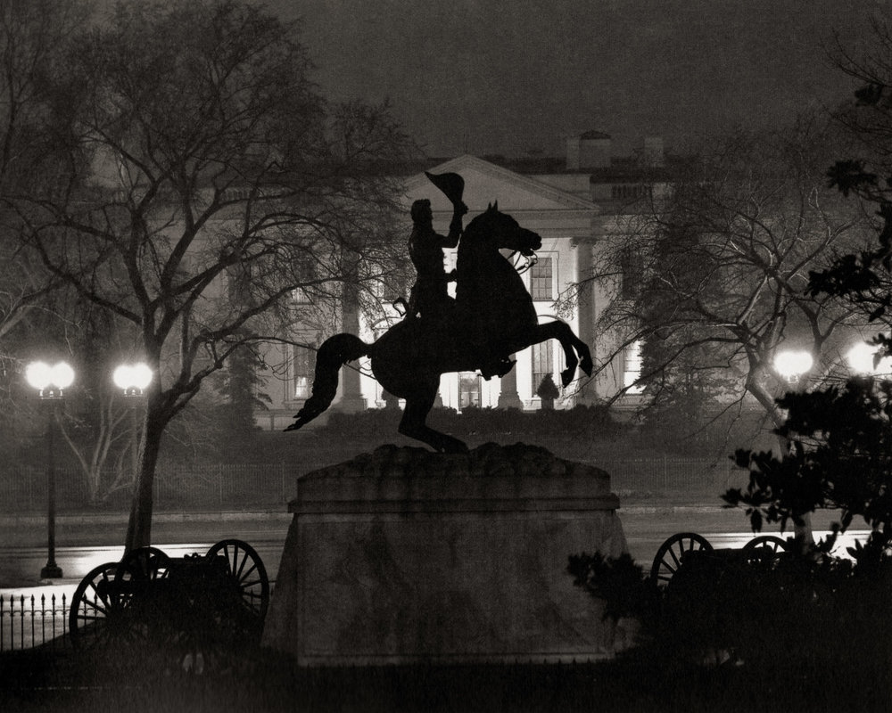 """""""Lafayette Square."""" A silhouetted sculpture of Andrew Jackson on a rearing horse opposite the North Portico of the White House. Wentzel used an exposure that kept the sculpture in shadow, but preserved the detail of the illuminated White House. As was typical of this series, Wentzel chose to photograph on a wet and foggy night, a strategy that he no doubt observed in the night work of Brassai, and perhaps in Stieglitz's as well."""