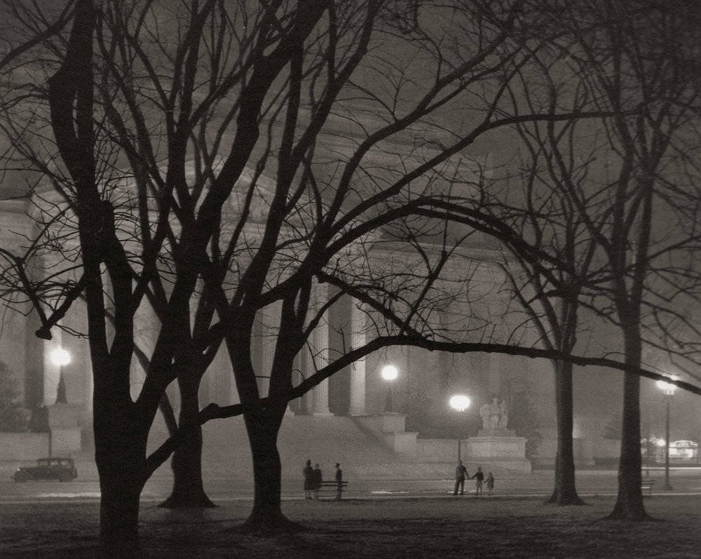 """National Archives."" The National Archives building had just been completed in 1935 when Wentzel made this image on a foggy night. Two groups of people illustrate the grand scale of the building, and the looming presence of the bare trees in the foreground add an air of mystery to the image."