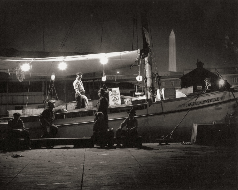 """The Waterfront."" The Washington canal was where fishermen delivered and sold their catch from the Chesapeake Bay to the restaurants and wealthy homes of Washington, D.C. In this image, a fisherman shows his catch to a customer in the shadow of the Washington Monument."