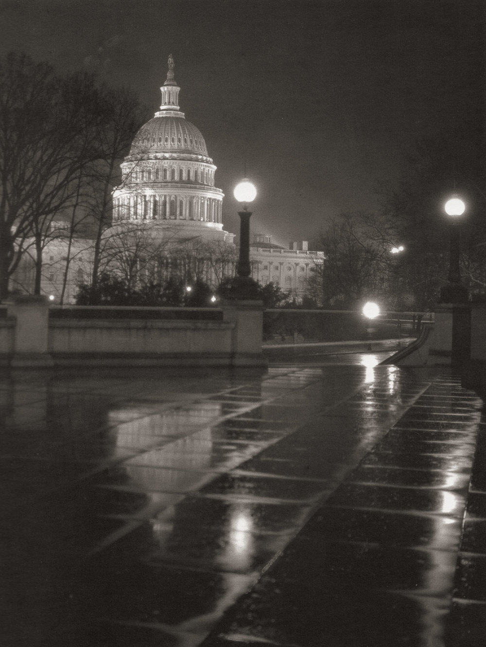 """U.S. Capitol."" Shot on a rainy night, the squares in the plaza reflect a darker side of the dome of the Capitol. There is a great irony in our majestic Capitol building–– the finial atop the dome is a nearly 20-foot statue of a woman titled ""Freedom,"" designed by sculptor Thomas Crawford, and cast in bronze by slave labor in 1863."