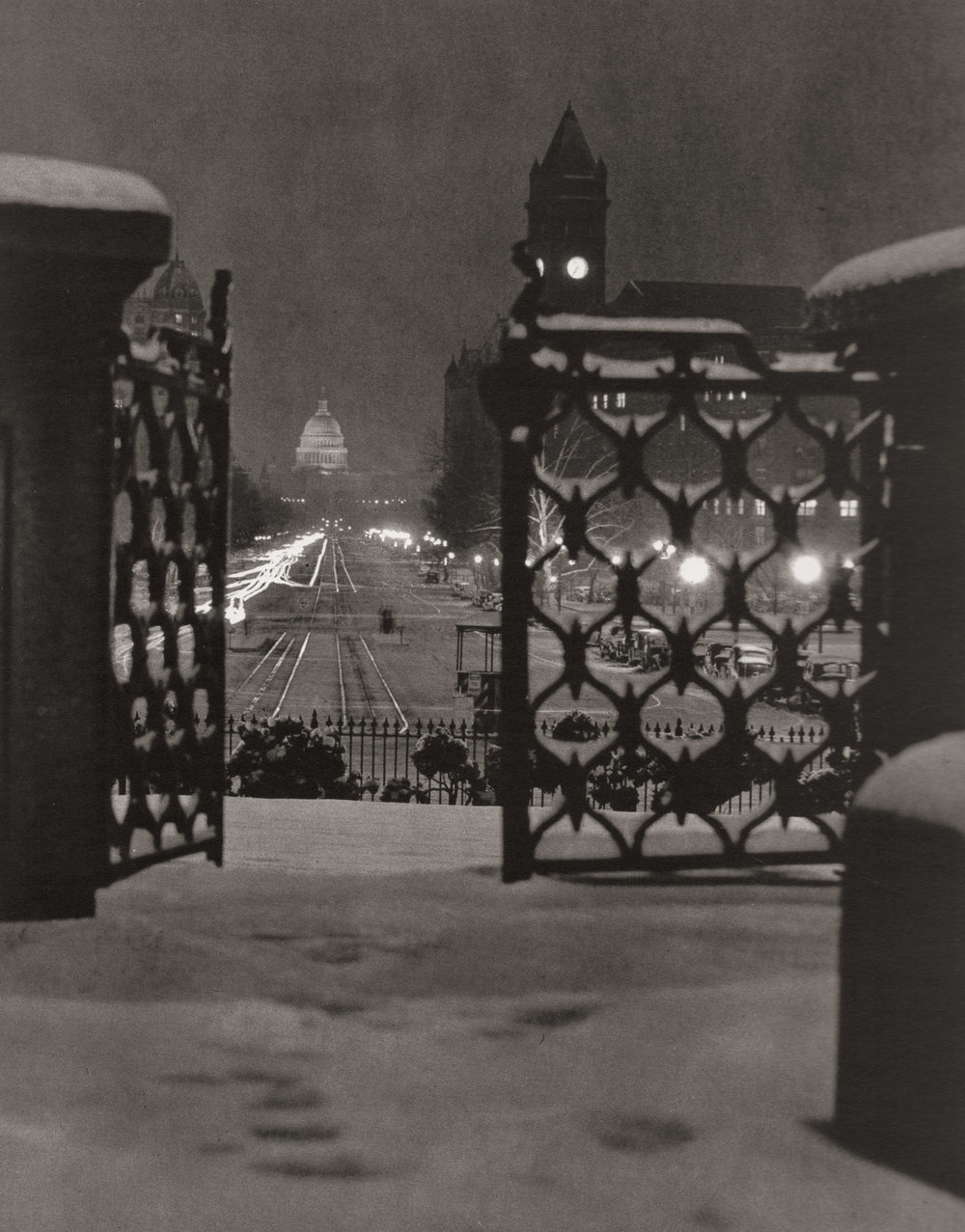 """Pennsylvania Avenue."" An image made on a snowy night from behind the gates of the Treasury building to the Capitol. Note the reflections off of the street car tracks, and the trails from car headlights, but not tail lights. Perhaps tail lights didn't yet exist in the 1930s, or they were so dim as to not register on Wentzel's film. The tower on the right is the old post office."