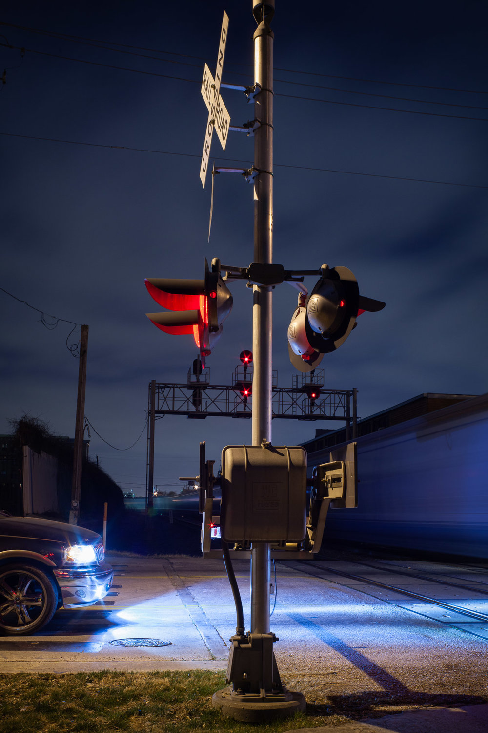 An SUV waits at the rail crossing, Houston, Texas, 2011.  Canon 5D Mark II  with a  50mm f/1.4  lens. 15 seconds, f/8, ISO 200. Everything came together in this spontaneous image–– the timing of the train, the composition and the lighting. The red warning light at the crossing provides a color accent and the cool xenon headlights of the SUV illuminate the passing train.