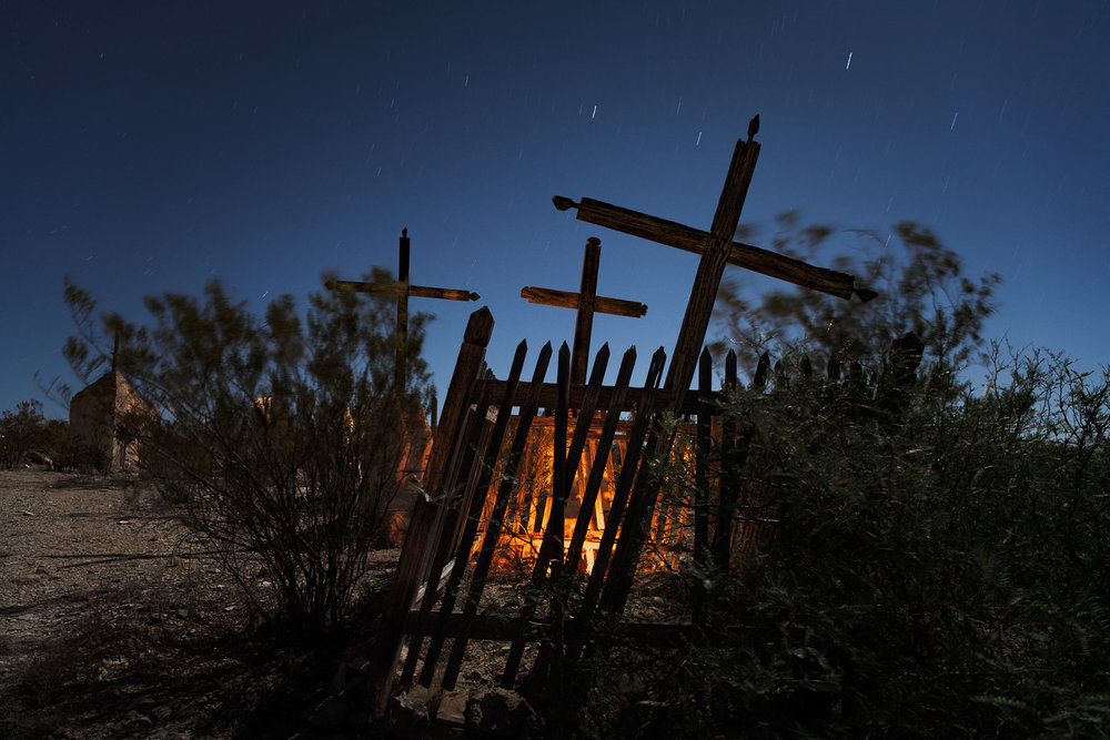 These two images were made nine years apart at the same location. The 2007 image was shot during a full moon at Dia de los Muertos, when candles illuminated many of the grave sites. The orange glow is from one such candle. There was no added light painting. Canon 5D and an adapted Nikon 28mm f/3.5 PC lens. 5 minutes, f/8, ISO 200.