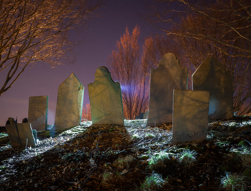 "Burial Hill in Plymouth, Massachusetts, is one of my favorite cemeteries. This image, made on top of the hill, shows trees lit by the sodium vapor lights of town, but the top of the hill is relatively dark except for some moonlight. The headstones were backlit with a  Coast HP7R  LED flashlight, with a little ""ghosting."" Image made in 2014. Canon 5D Mark II and an adapted Nikon 28mm f/3.5 PC lens. 4 minutes, f/5.6, ISO 100."