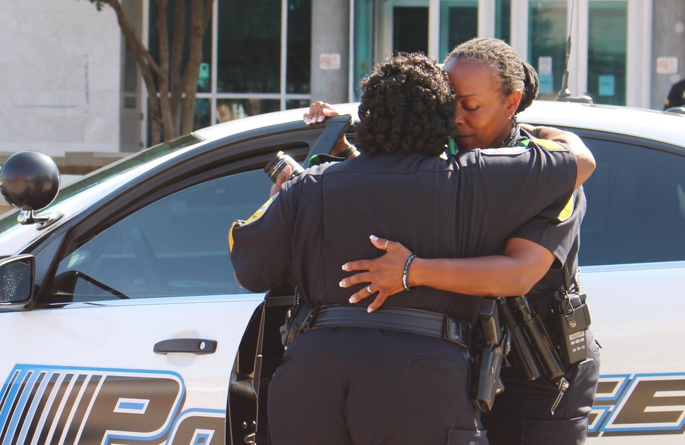Two officers embrace in an emotional hug following a moment of silence in front of DPD headquarters.