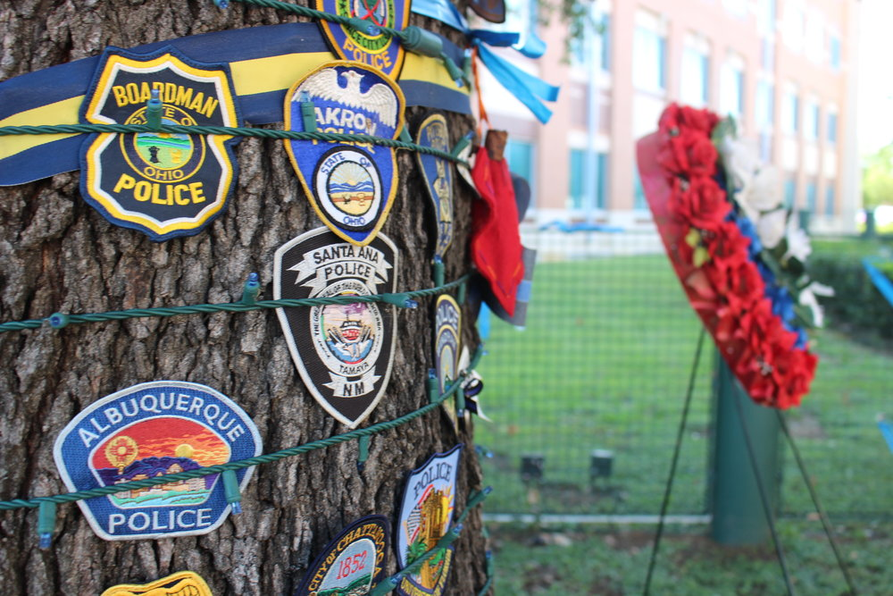 In a show of support, police badges from across the nation could be found pinned to a tree at a memorial on DPD grounds.
