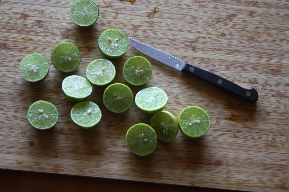 Key Limes sliced on a wooden cutting board