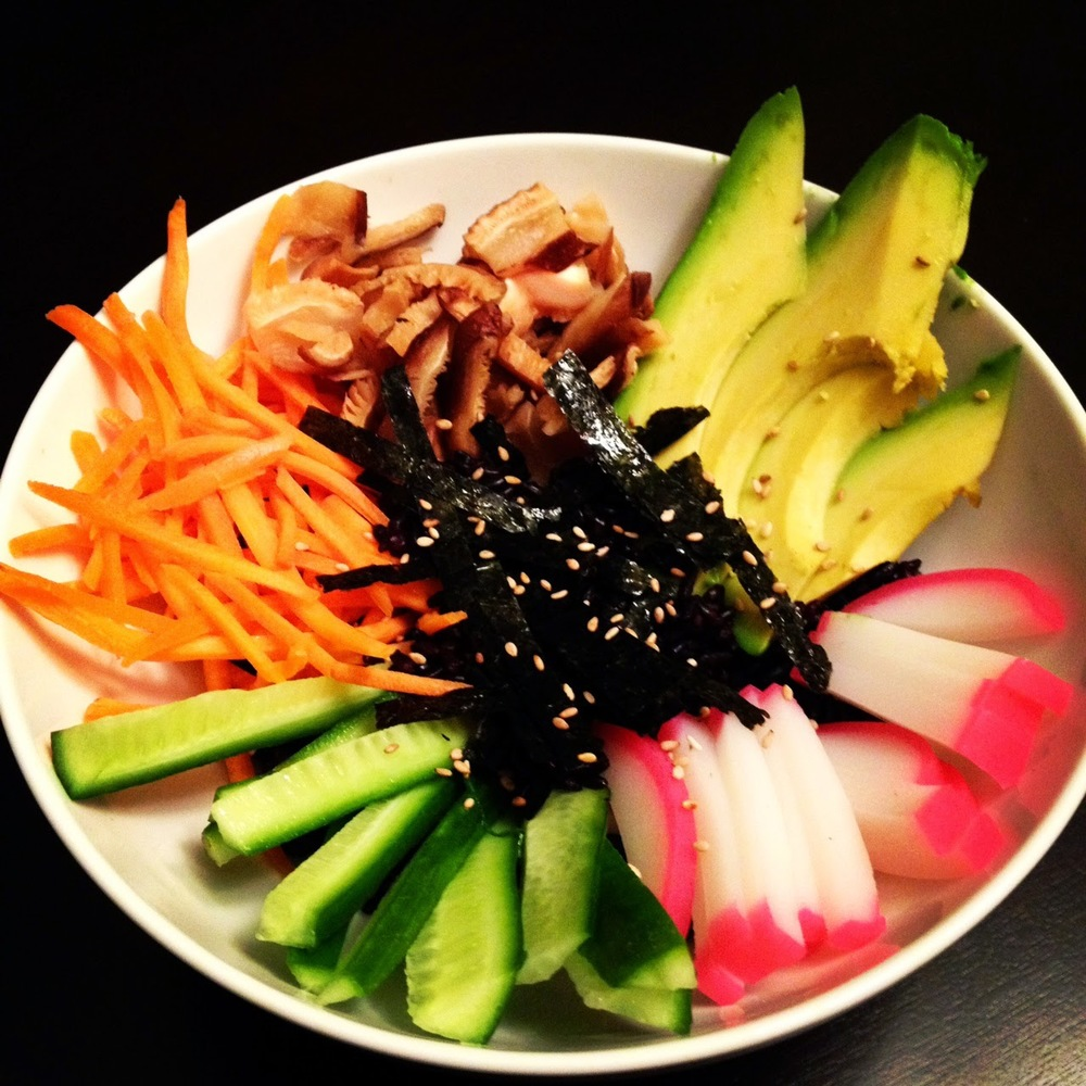 Avocado, cu cucumber, carrots, kamaboko, shiitake mushrooms and nori over a bed of black rice.
