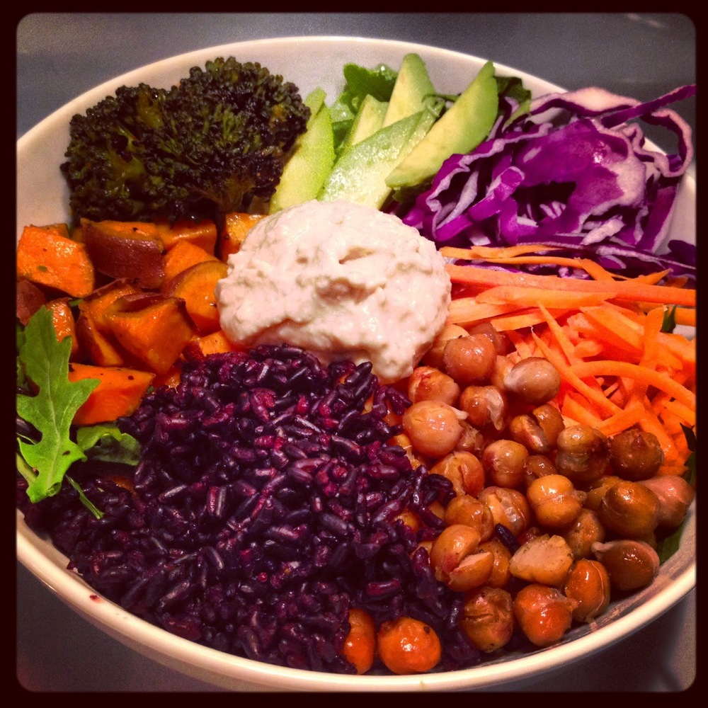 Roasted sweet potatoes, avocado, forbidden black rice, roasted chickpeas, carrots, roasted broccoli, red cabbage and hummus on a bed of organic arugula.