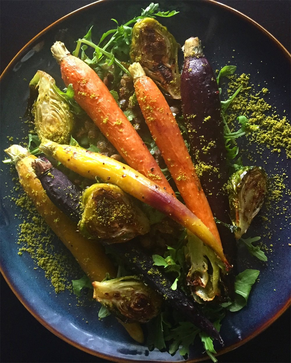 Roasted carrots, brussel sprouts, and lentils on a bed of arugula. Sprinkled with leek brioche.