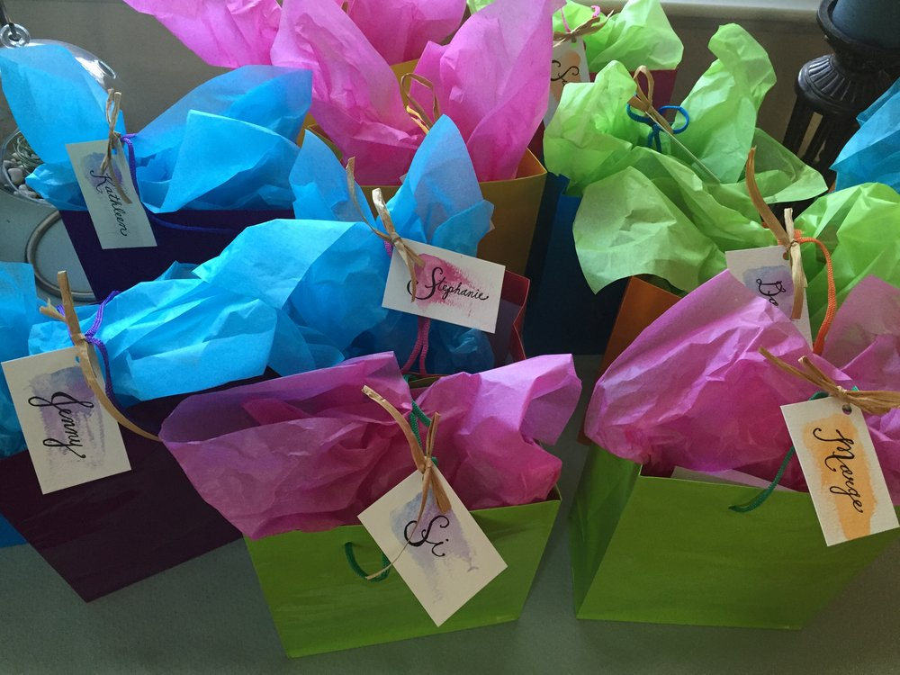 Personalized gifts bags filled with Numi Tea, Square Organics bars, homemade aquafaba cookies, and a seasonal produce list.