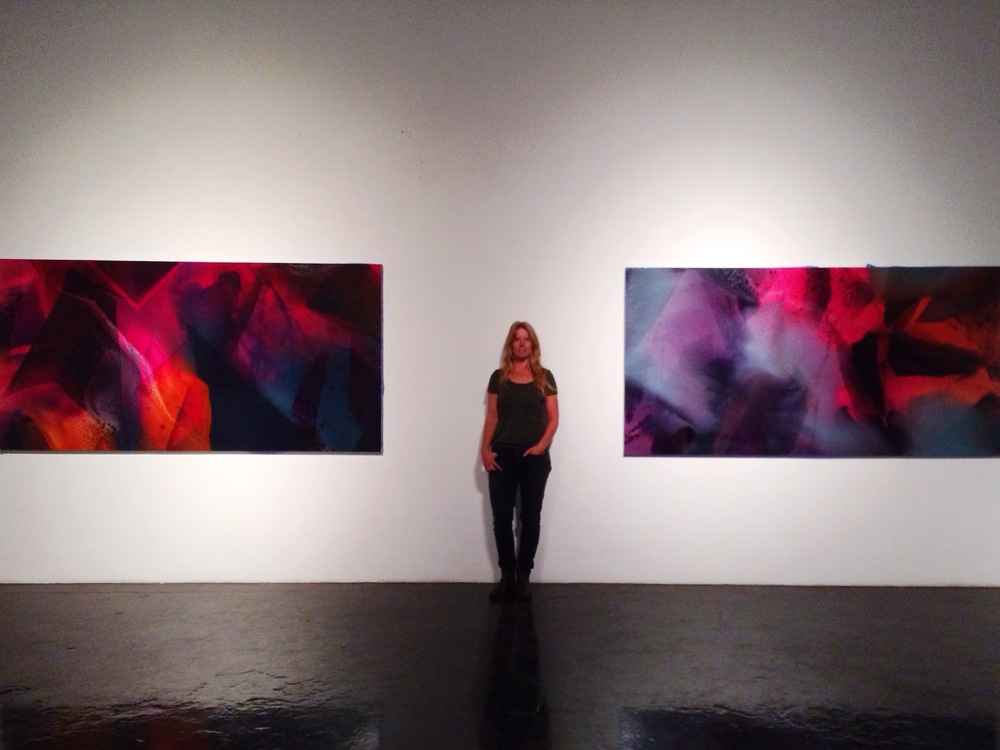 "Artist, Jennifer Wolf with her paintings, ""Time Place Continuum"" and ""Spring Theory"""