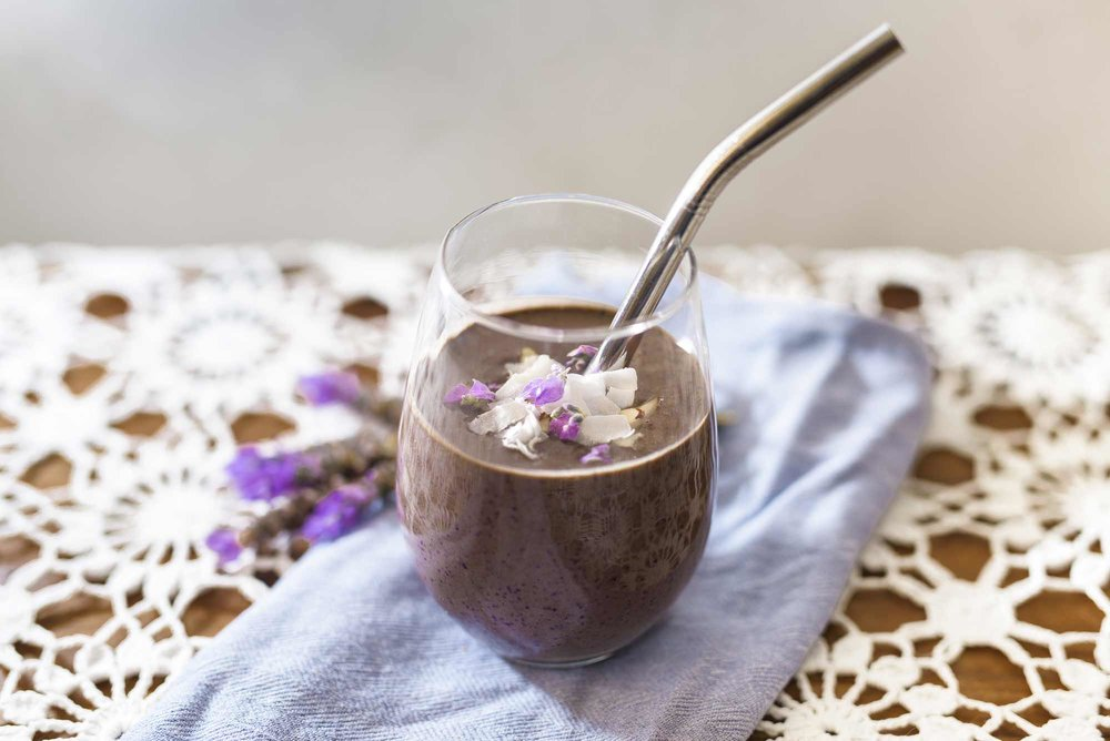 Blueberry cacao smoothie, so delicious. Garnished here with slithered almonds, dried coconut slithers and lavender petals.