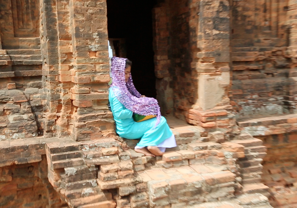 A Cham woman dresses up to pose for tourist pictures