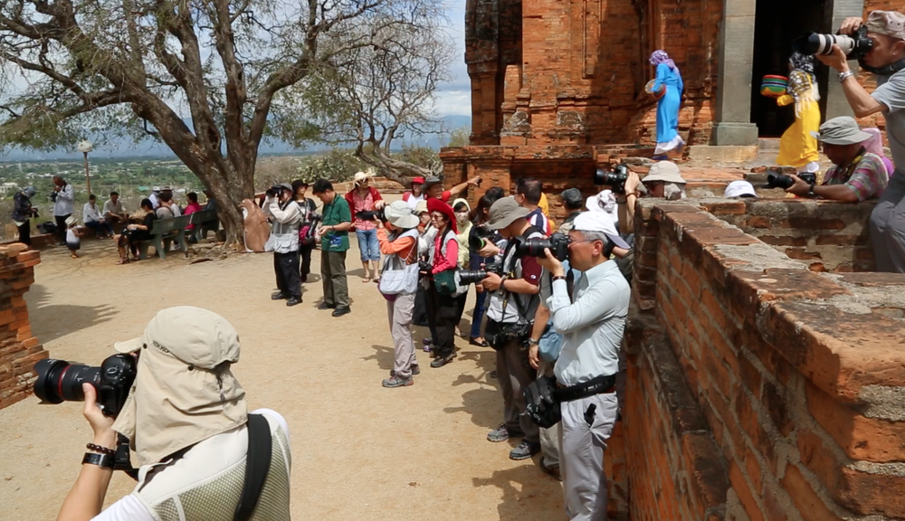Group of Chinese tourists taking pictures of the local women