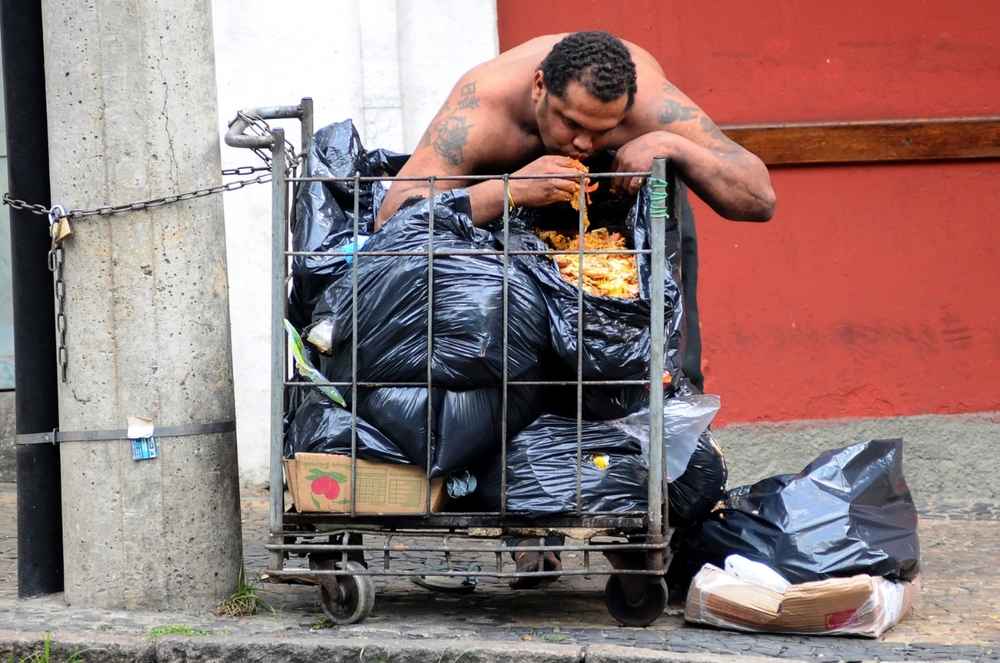 Homeless person with mental problems eatingwasted food from a restaurant;Brazil. ©Erica Dezonne / All rights reserved