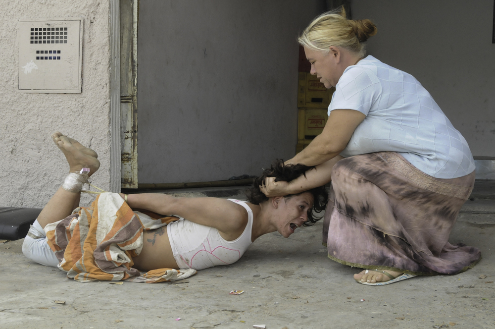 Sueli Juiz da Costa holds her daughter Fernanda, 24, while she is having hallucinations caused by crack addiction; Brazil. ©Erica Dezonne / All rights reserved