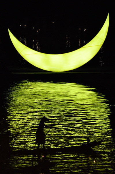 A fisherman  silhouette and the moon . Impression Sanjie Liu, Li River. China, 2014.