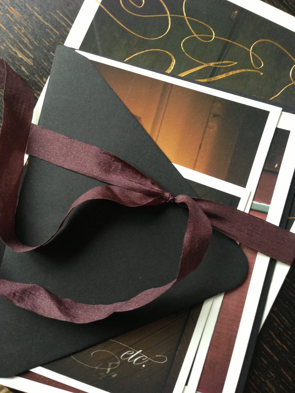 The invitation features cards of different sizes each printed with a photo of a door from the property and bound with a vintage eggplant colored ribbon.